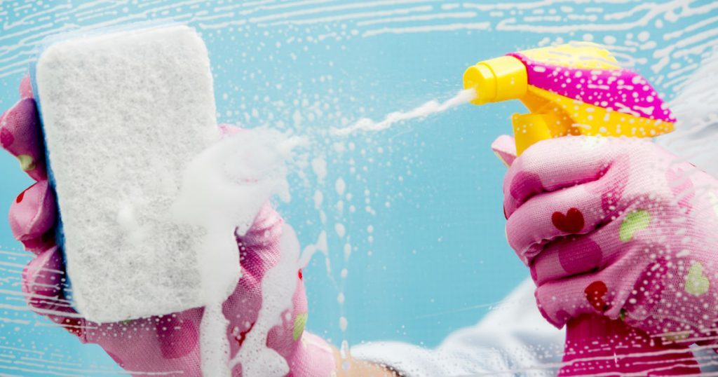Close-Up of spray bottle spraying cleaning fluid and sponge